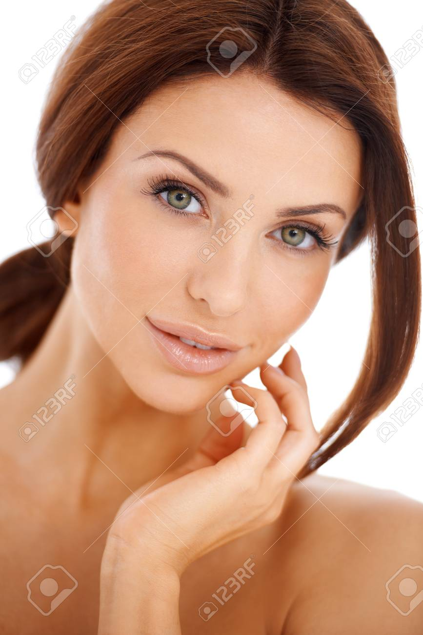 Head and shoulders studio portrait of a beautiful natural woman looking at the camera with her long brunette hair tied back neatly isolated on white Stock Photo - 17968917