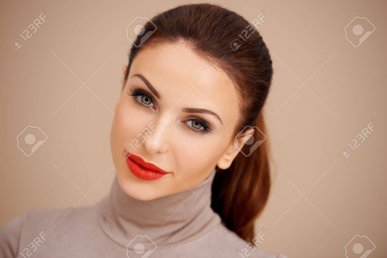 Gorgeous beautiful brunette with her hair tied back in a ponytail wearing a poloneck and red lipstick  studio headshot on a beige background Stock Photo - 17968899