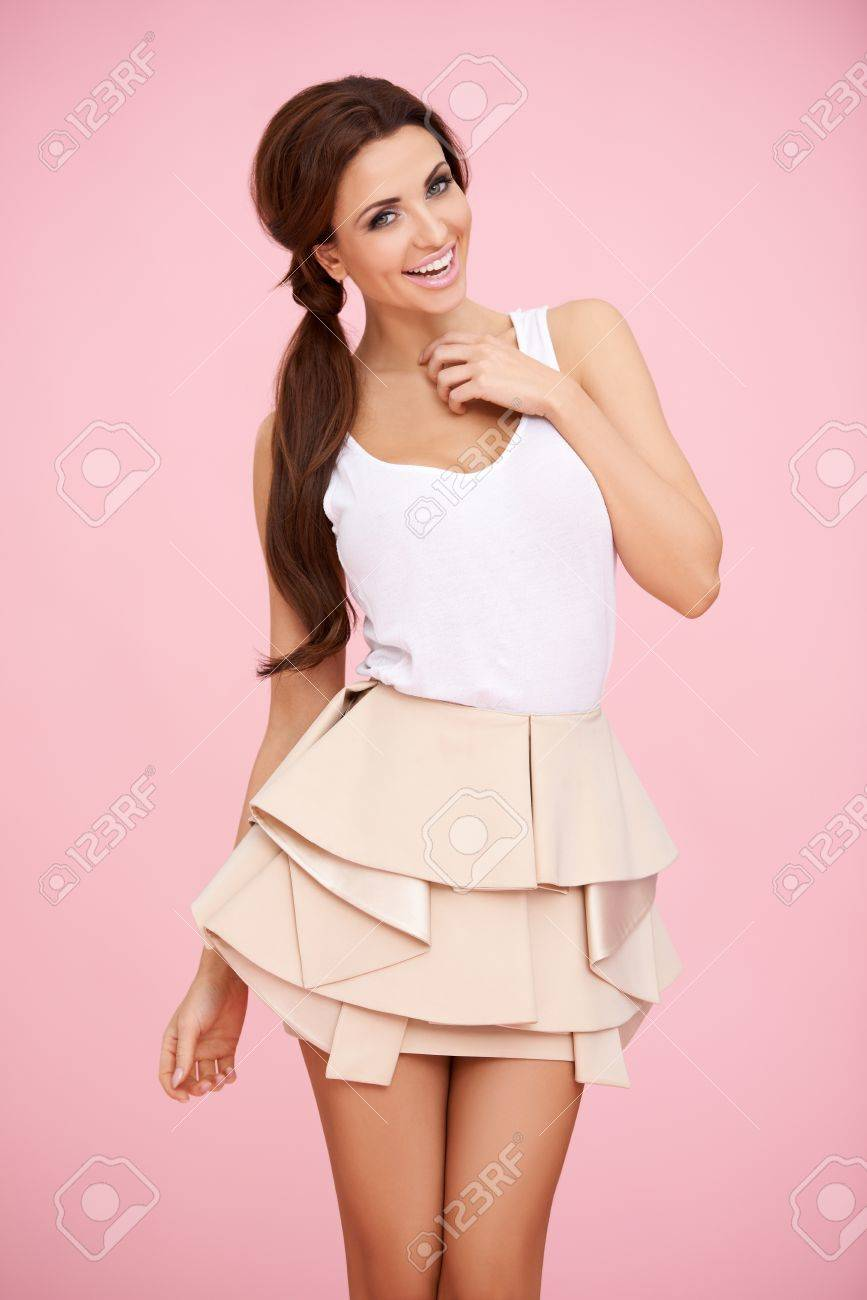 Cute brunette in a short skirt posing before pink background Stock Photo - 17968830