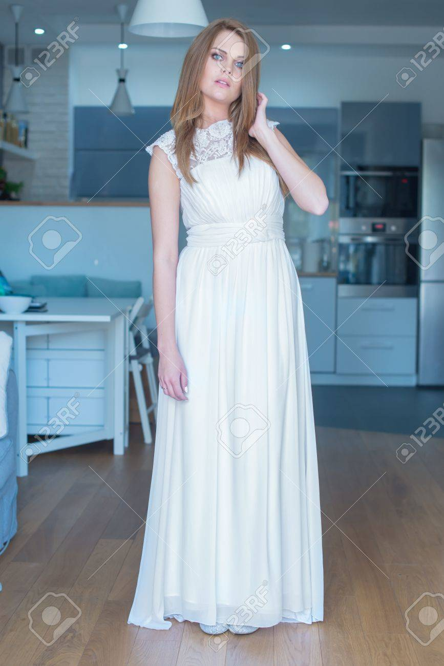 Woman In Long White Wedding Dress Standing In Kitchen With Hand ...