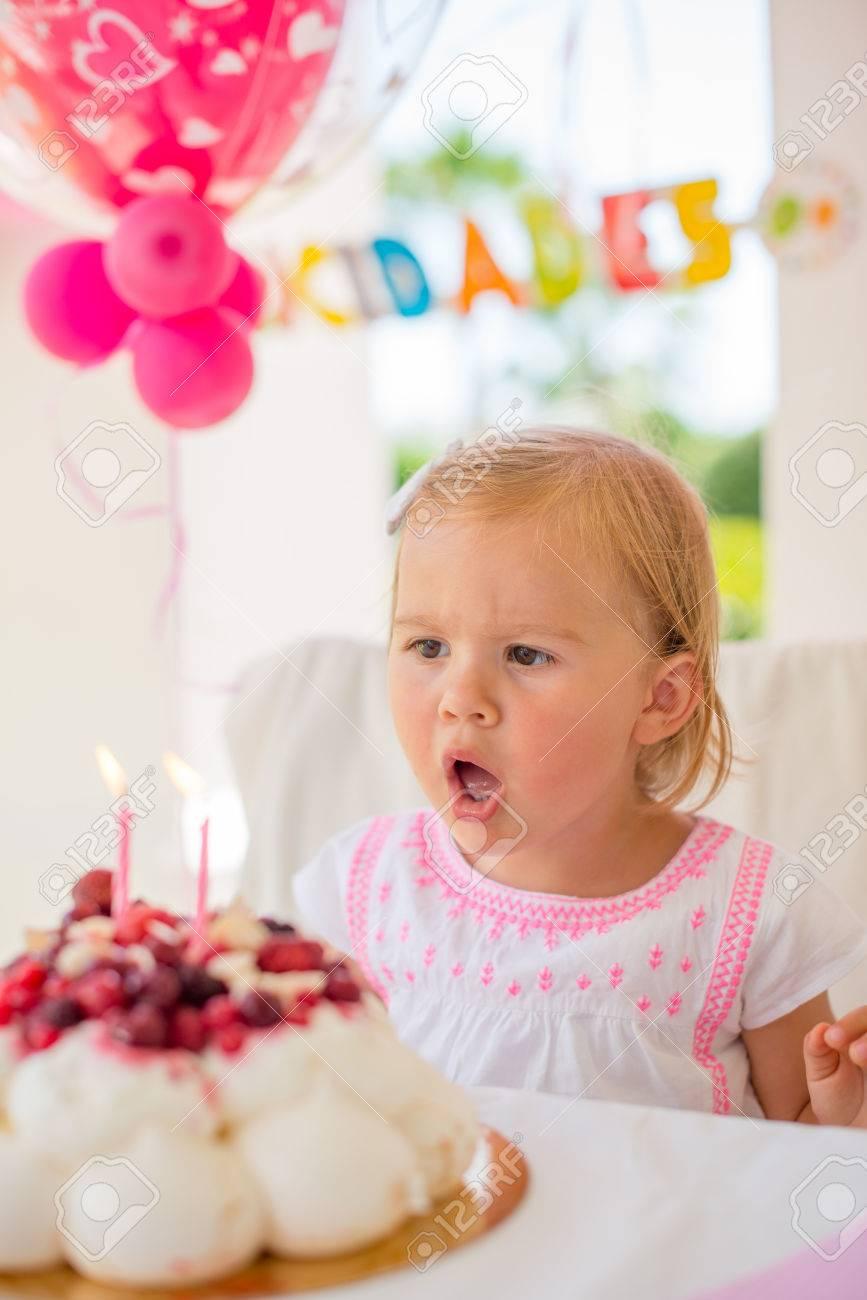 Niña Linda Que Sopla Las Velas De Su Partido Al Aire Libre De La Torta De Cumpleaños Brillante Terraza Con La Decoración Rosada