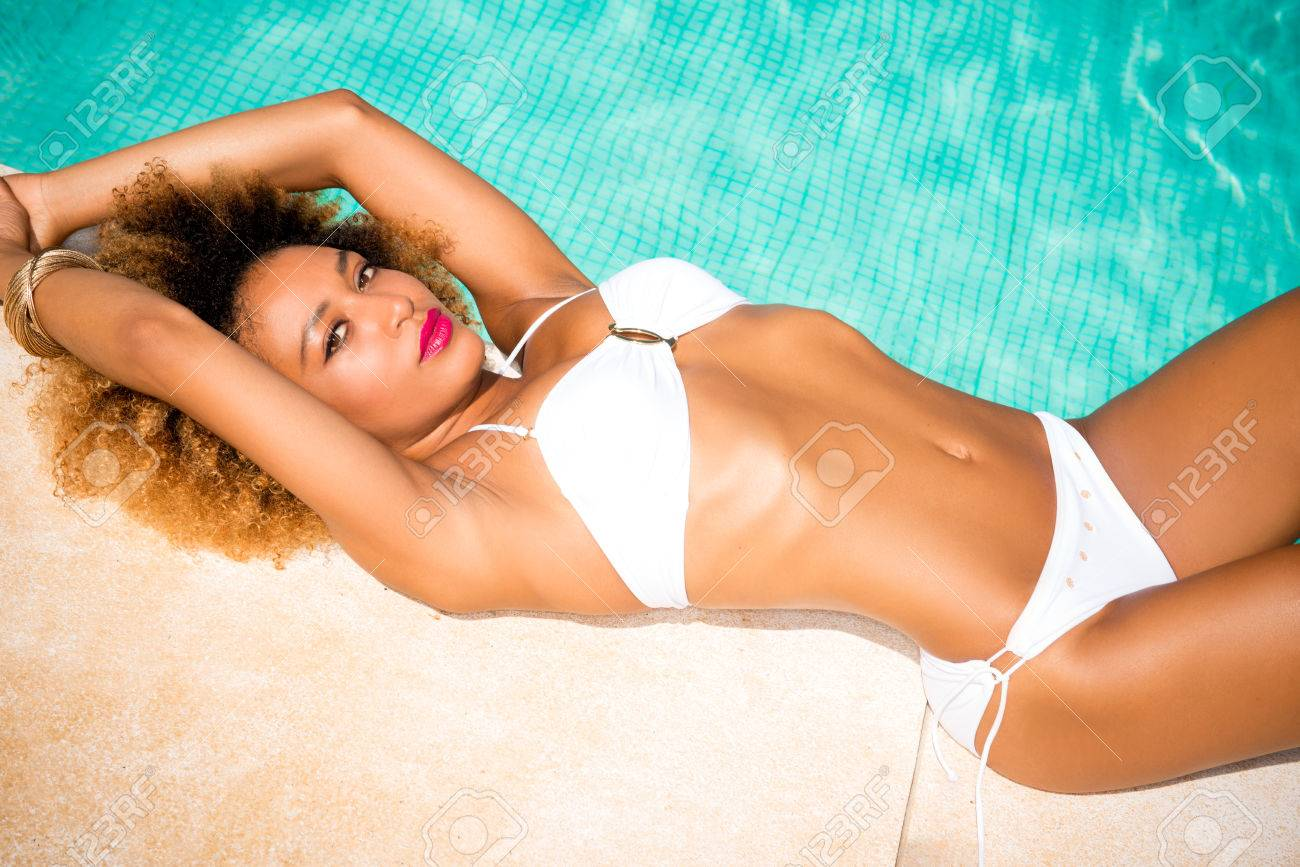 b90e867cb14 Sexy Model with Afro Haircut Posing Next to Exotic Swimming Pool She  Wearing White Skimpy Bikini