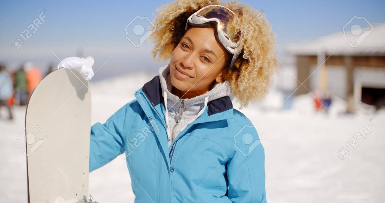 44ca2de84c Gorgeous trendy young woman posing with her snowboard at a winter ski  resort standing in the