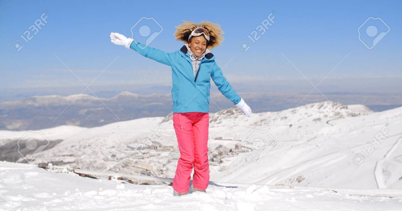 49f9a2e1f3 Happy beautiful young adult female in pink and blue skiing outfit waving  arms around in the