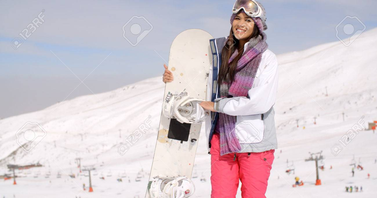 68cb8a356b Smiling gorgeous young woman in ski clothes and goggles posing with her  snowboard on a snowy