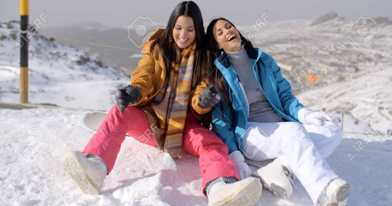 12a28a4c52 Stock Photo - Two young female snowboarders enjoying a chat as they sit  alongside a high mountain run at a ski resort relaxing on a snowboard  smiling and ...