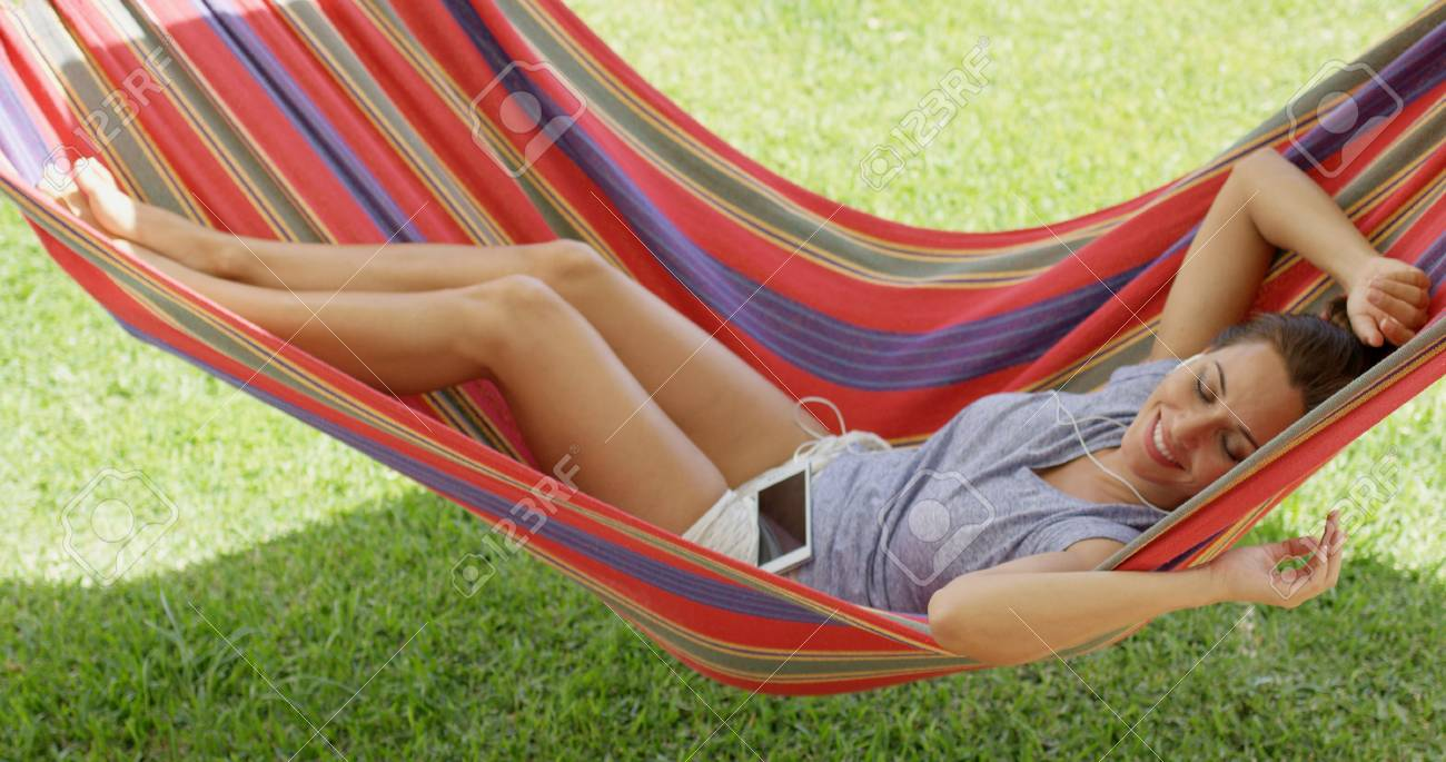 happy young woman relaxing in a colorful hammock outdoors in stock