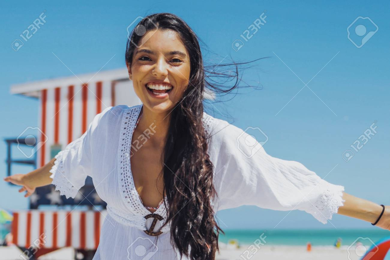 Young excited girl in white dress laughing happily at camera having fun on sunny tropical beach on background of blue sky. - 98350181