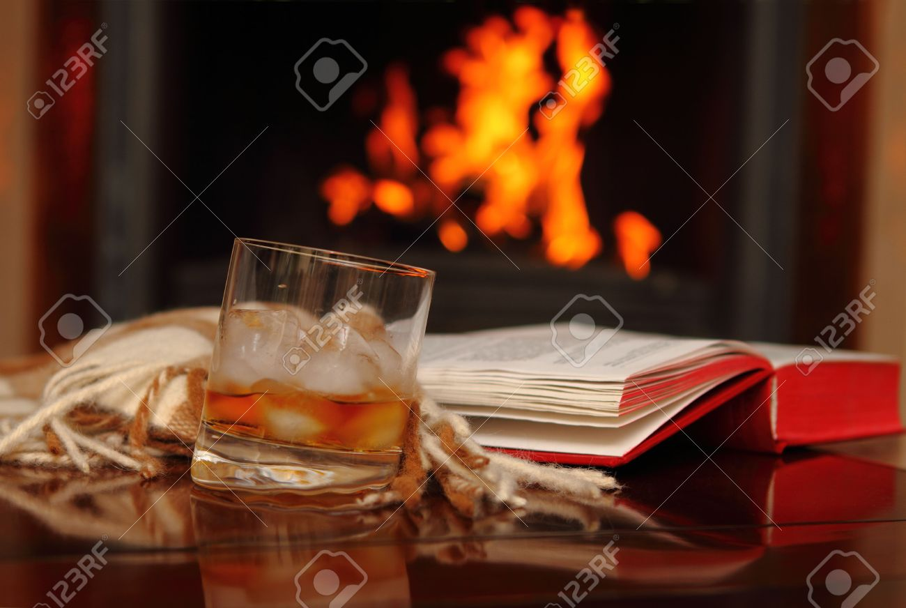 whiskey book and shawl by the fireplace stock photo picture and