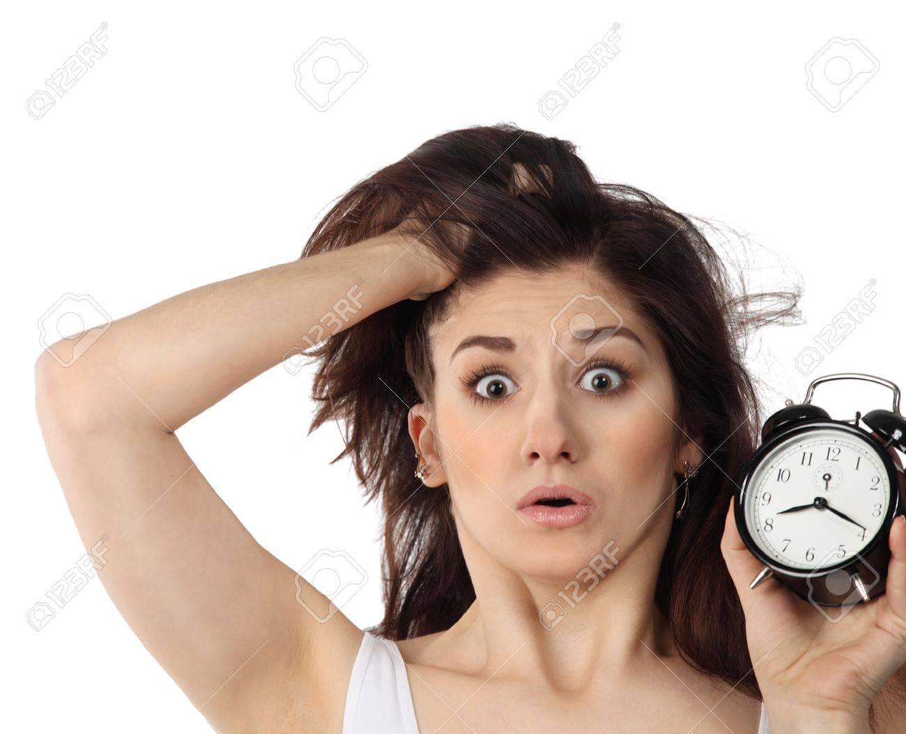 Surprised young brunette woman holding clock in her handin amazement Stock Photo - 12285195