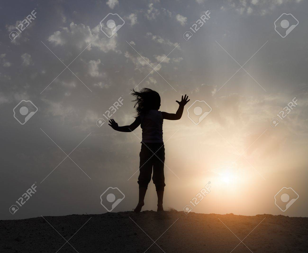 Little happy girl jumping on the beach in sunset time Stock Photo - 13410063