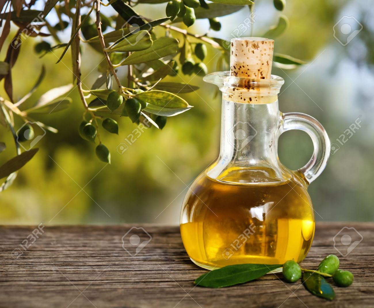 Olive oil and olive branch on the wooden table over nature background - 18363507