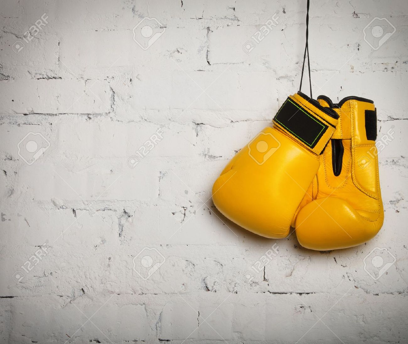 Pair of yellow boxing gloves hanging on a brick wall Stock Photo - 18941955