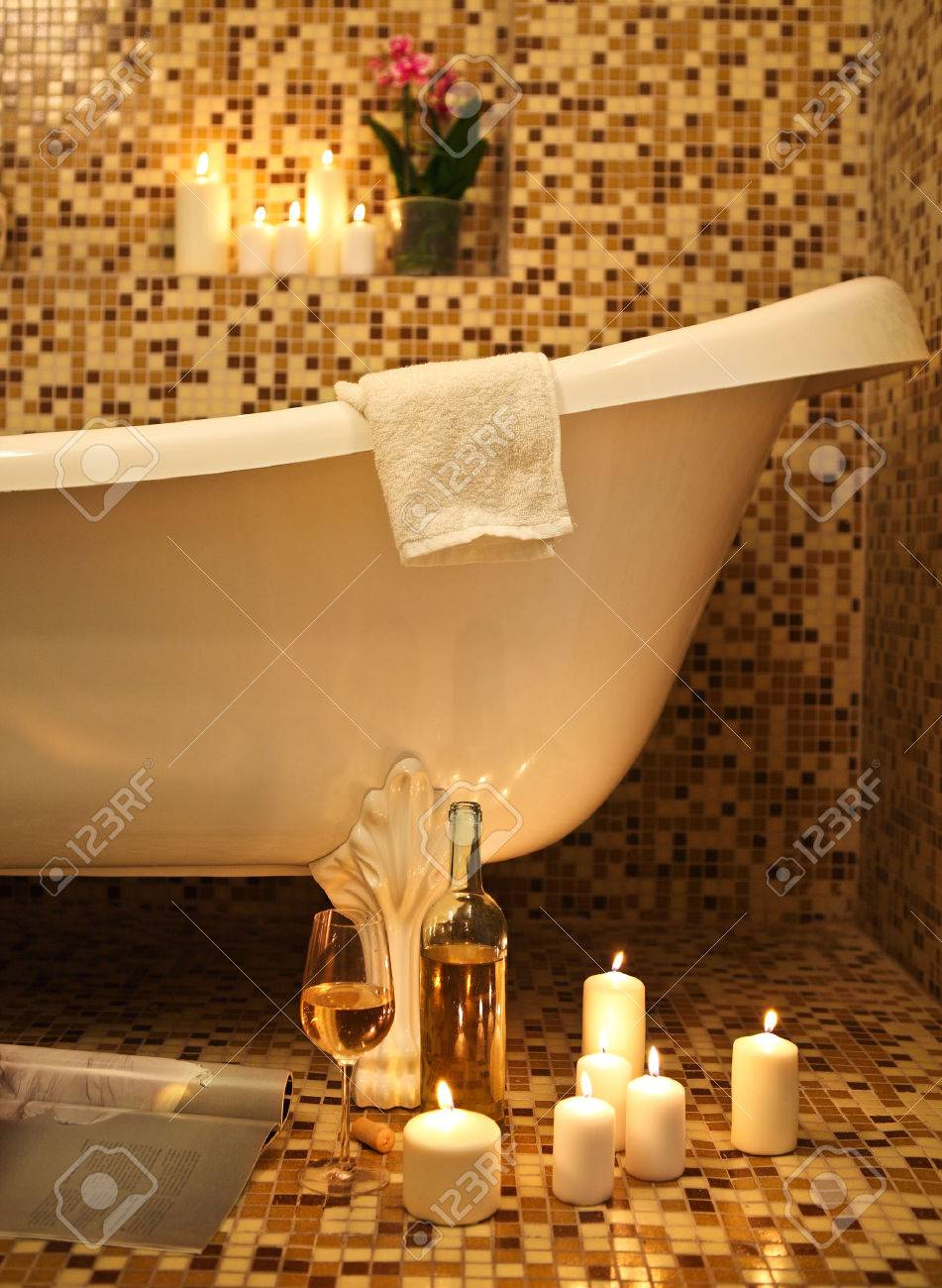 Home Bathroom Interior With Bubble Bath, Candles, Magazine And White Whine.  Relax Concept