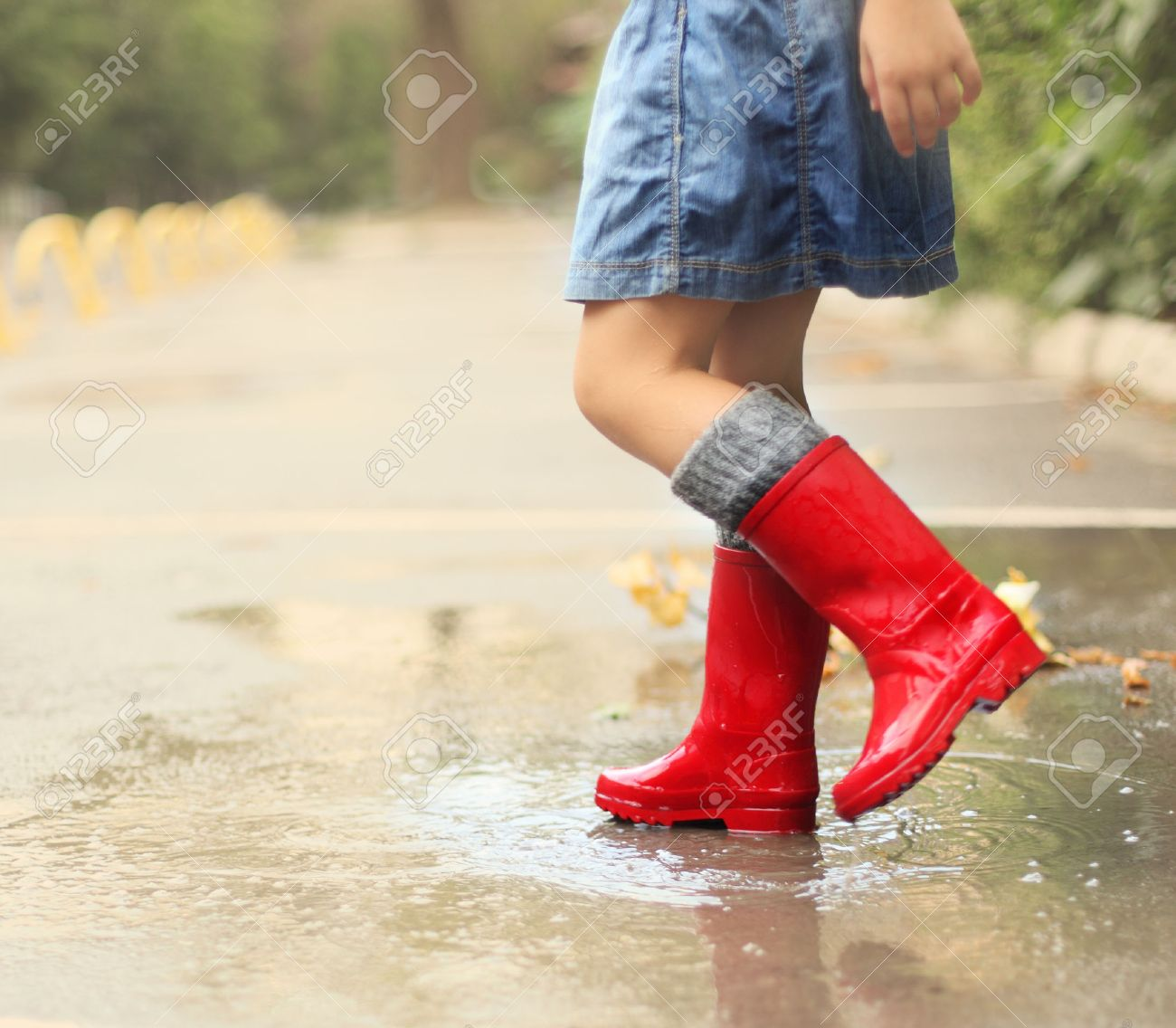 Child Wearing Red Rain Boots Jumping Into A Puddle. Close Up Stock ...