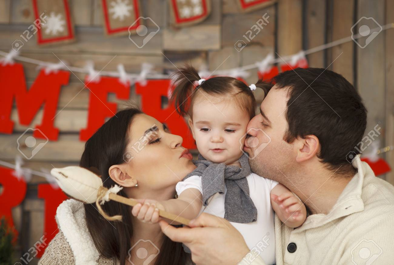 Happy smiling family with one year daughter near the Christmas background Stock Photo - 22608449