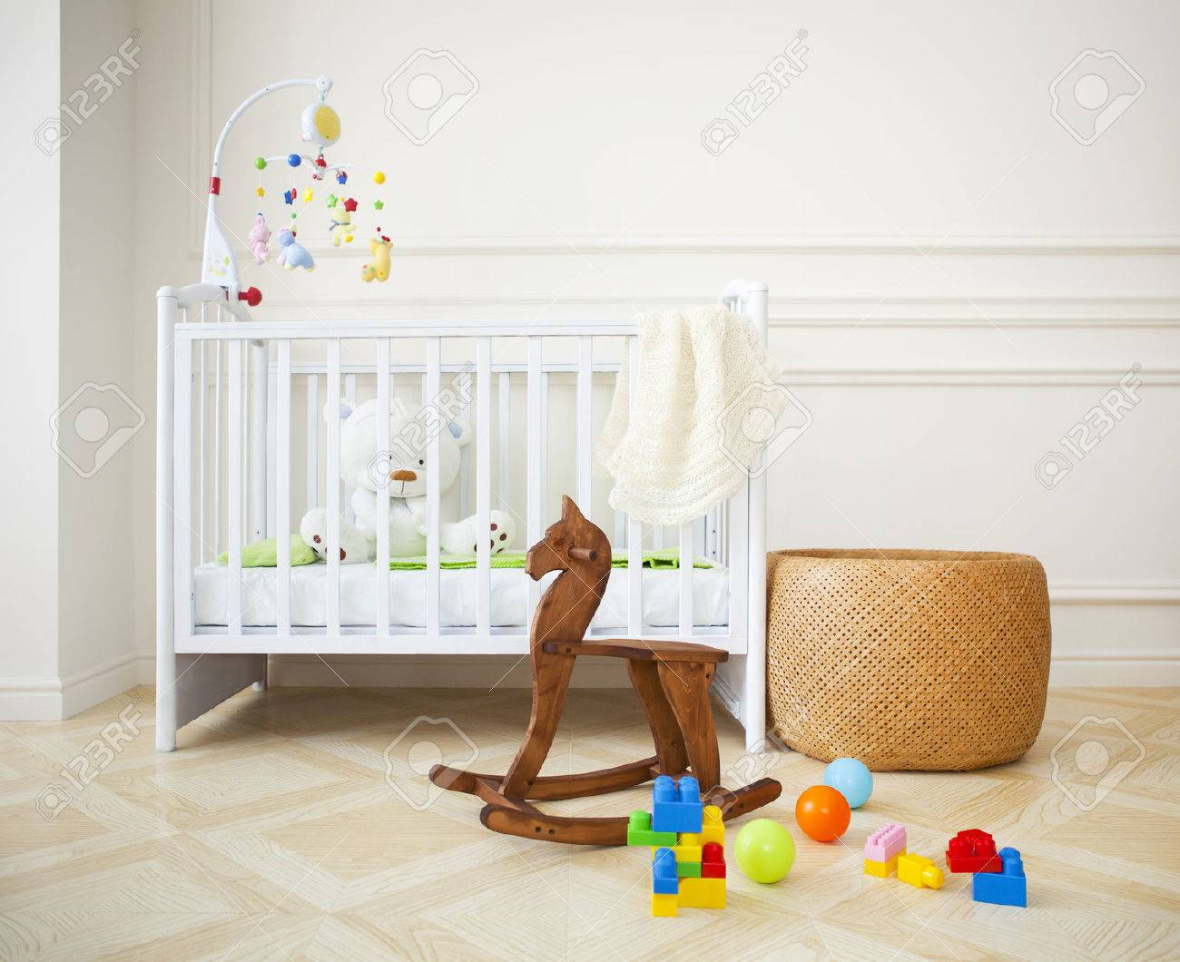 Empty nursery room with basket, toys and wooden horse Stock Photo - 31637897