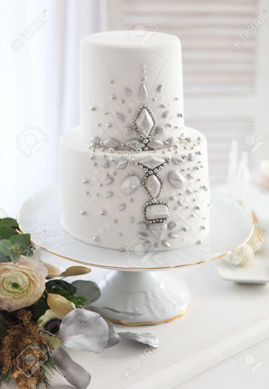Gâteau De Mariage Blanc Avec Une Décoration Argent Et Bouquet De Mariage Avec Renoncules