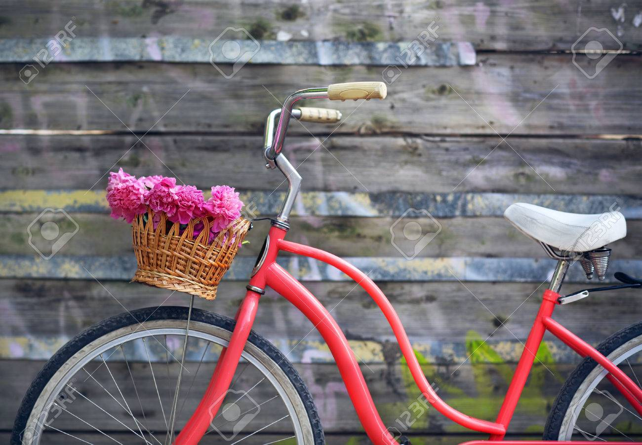 Vintage bicycle with basket with peony flowers near the old wooden wall - 36322718