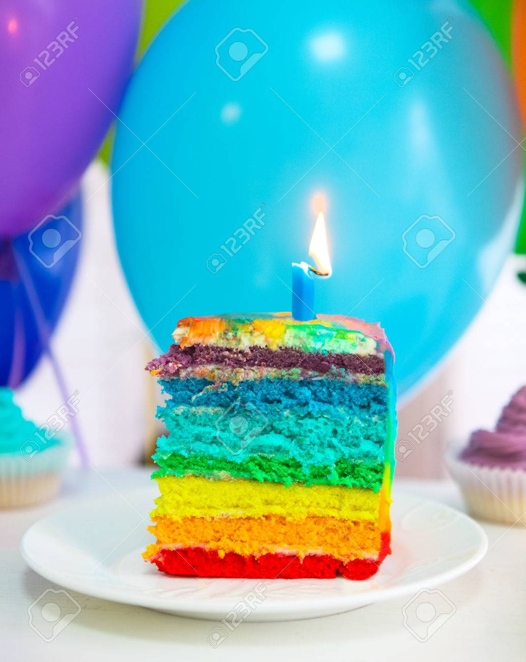 Rainbow Cake Decorated With Birthday Candle Balloons On The Background Stock Photo