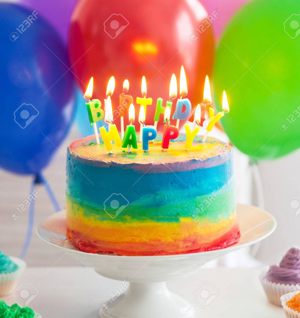 Rainbow Cake And Cupcakes Decorated With Birthday Candles Balloons On The Background Stock Photo
