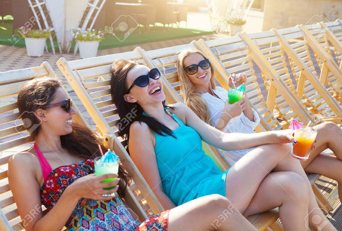 Happy girls with beverages on summer party near the pool - 36867590