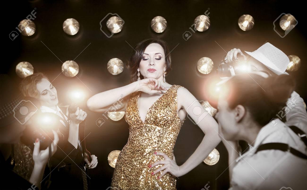 Superstar woman wearing golden shining dress posing to paparazzi - 37650903