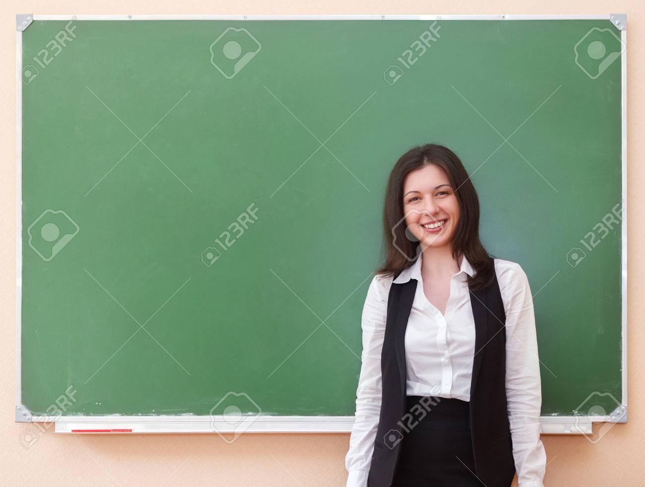 Student girl standing near clean blackboard in the classroom - 38253515