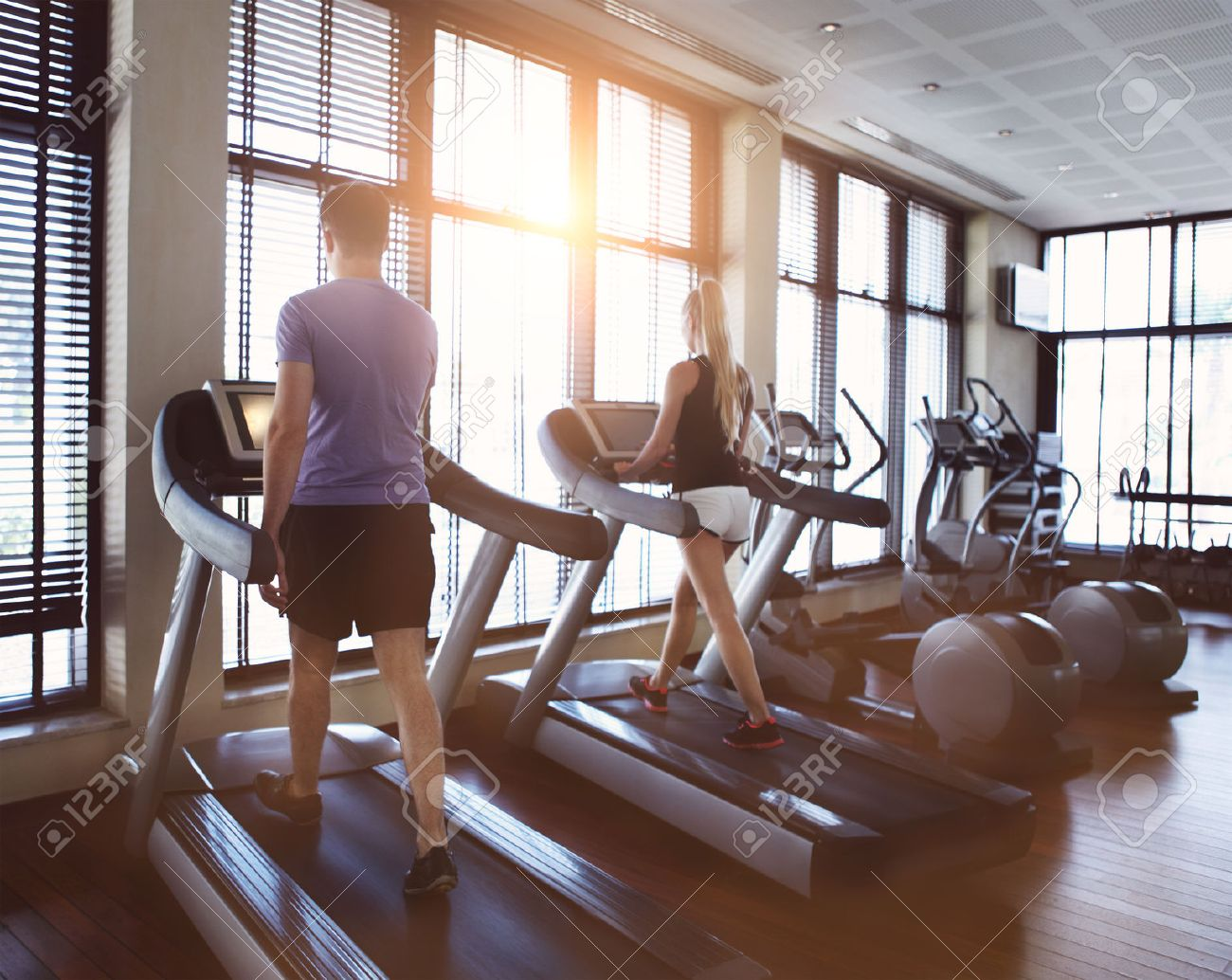 Healthy man and woman running on a treadmill in a gym. Sport and health concept - 40375927