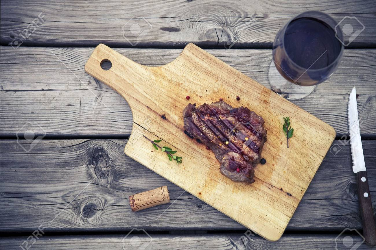BBQ steak. Barbecue grilled beef steak meat with red wine and knife. Healthy food. Barbeque steak dinner - 40572869