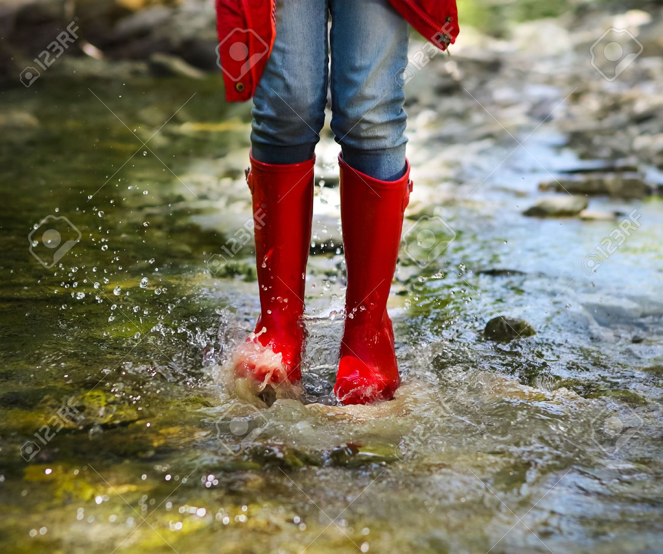 Child Wearing Red Rain Boots Jumping Into A Mountain River. Close ...