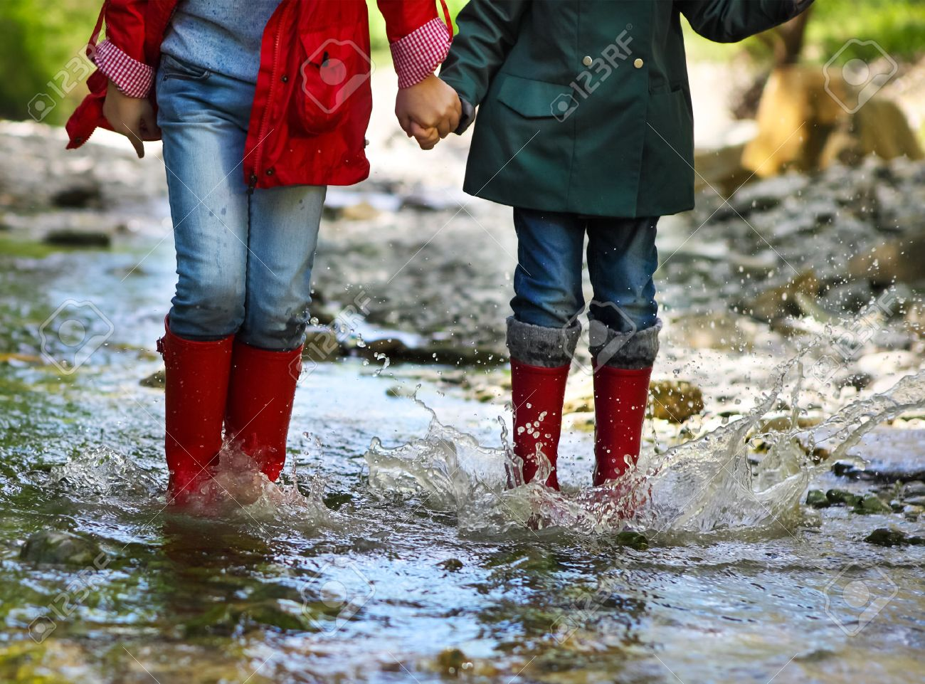 Children wearing rain boots jumping into a mountain river. Close up - 40573095