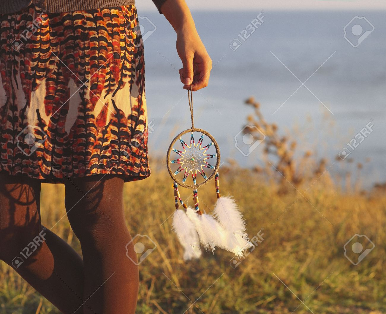 Brunette woman with long hair holding dream catcher in her hands - 42278076
