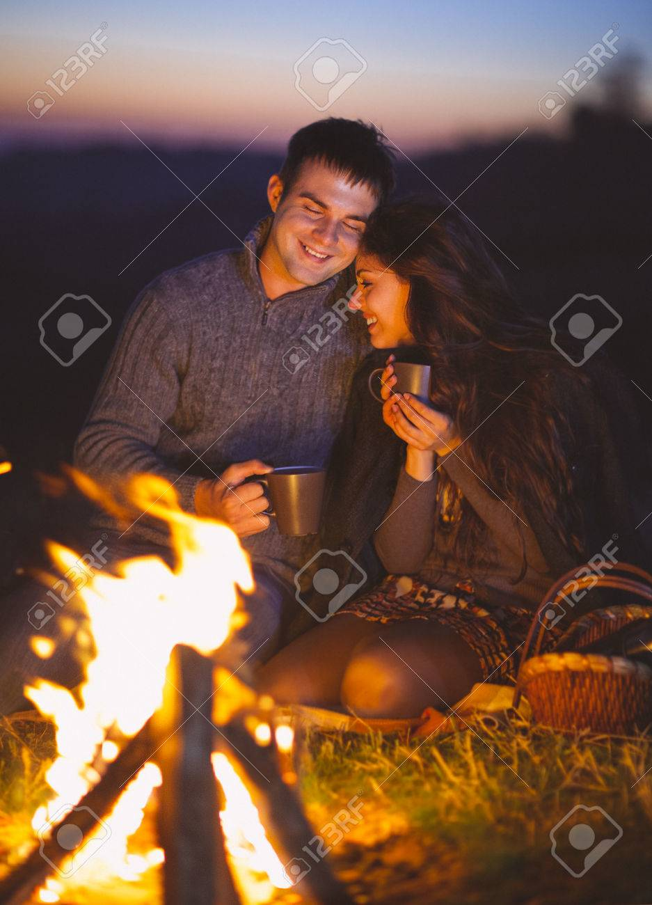 Portrait of the happy couple sitting by fire on autumn beach at the night - 42278103