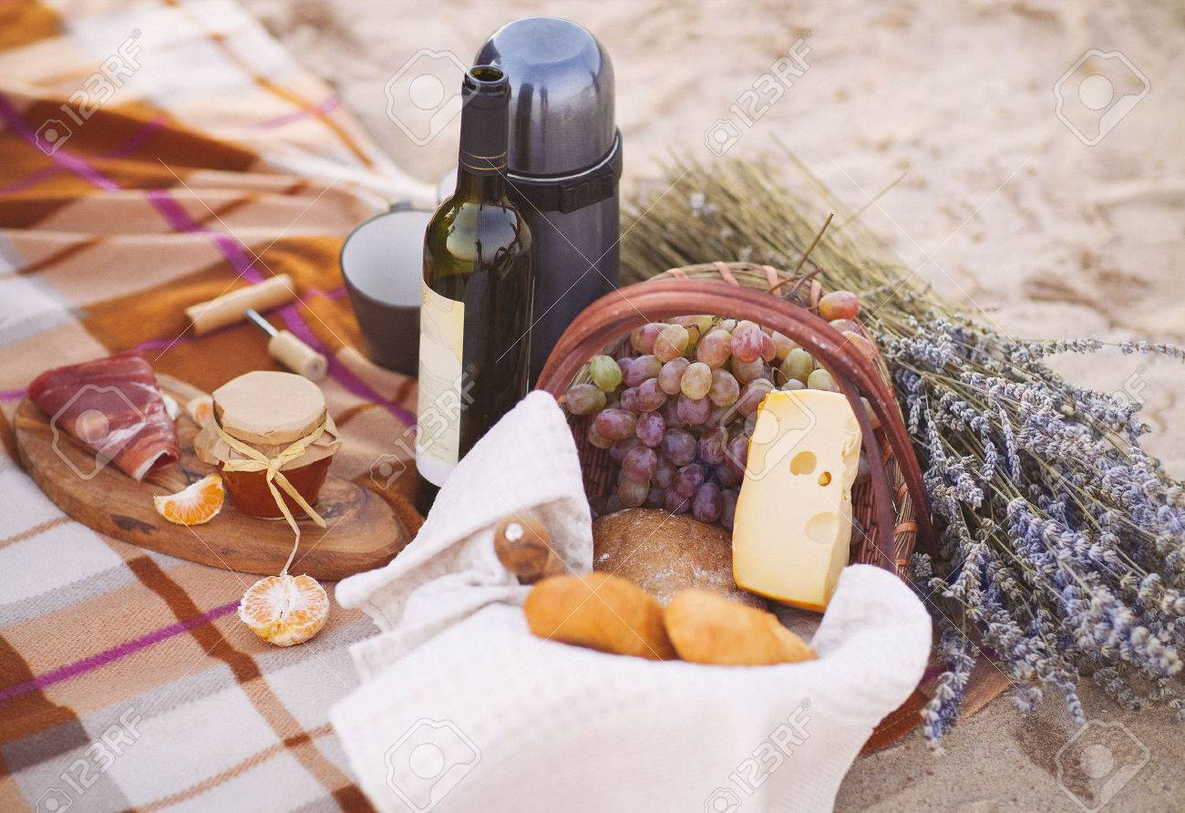 Autumn picnic by the sea with wine, grapes, bread, jam and cheese - 42426775