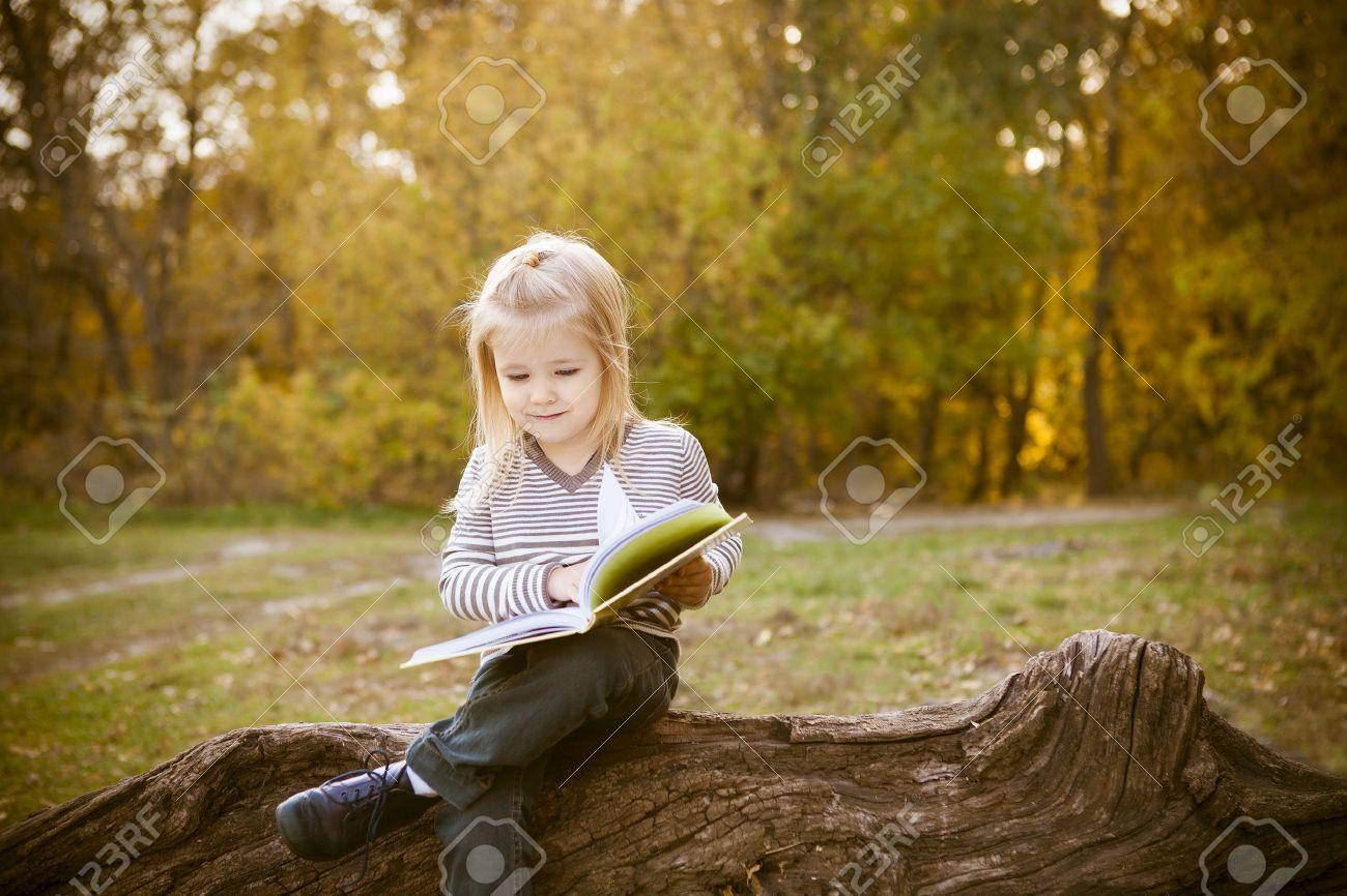 Cute little girl reading a book in autumn park - 44363272
