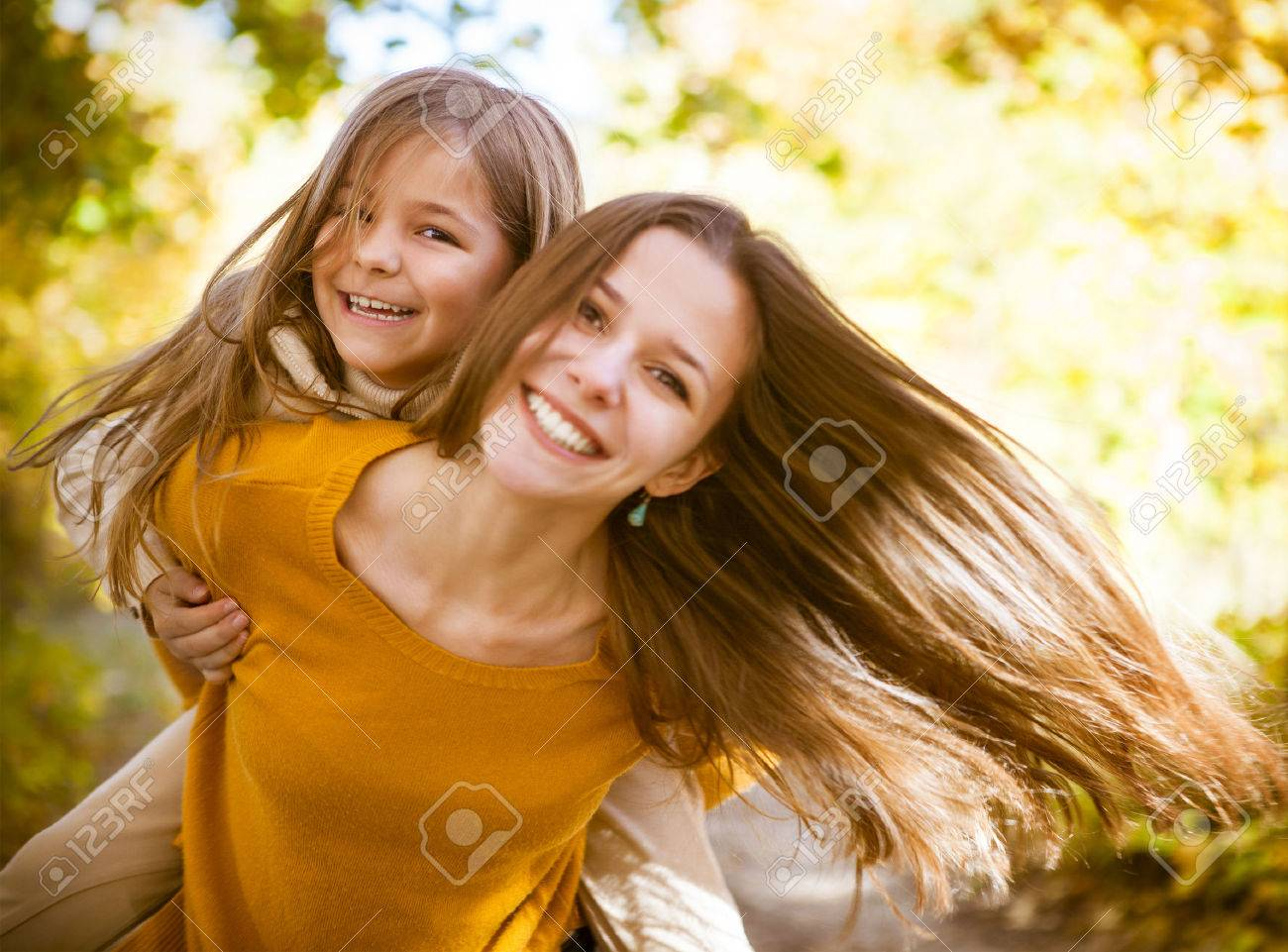 Two cheerful sisters playing in the park in warm autumn day - 44363268