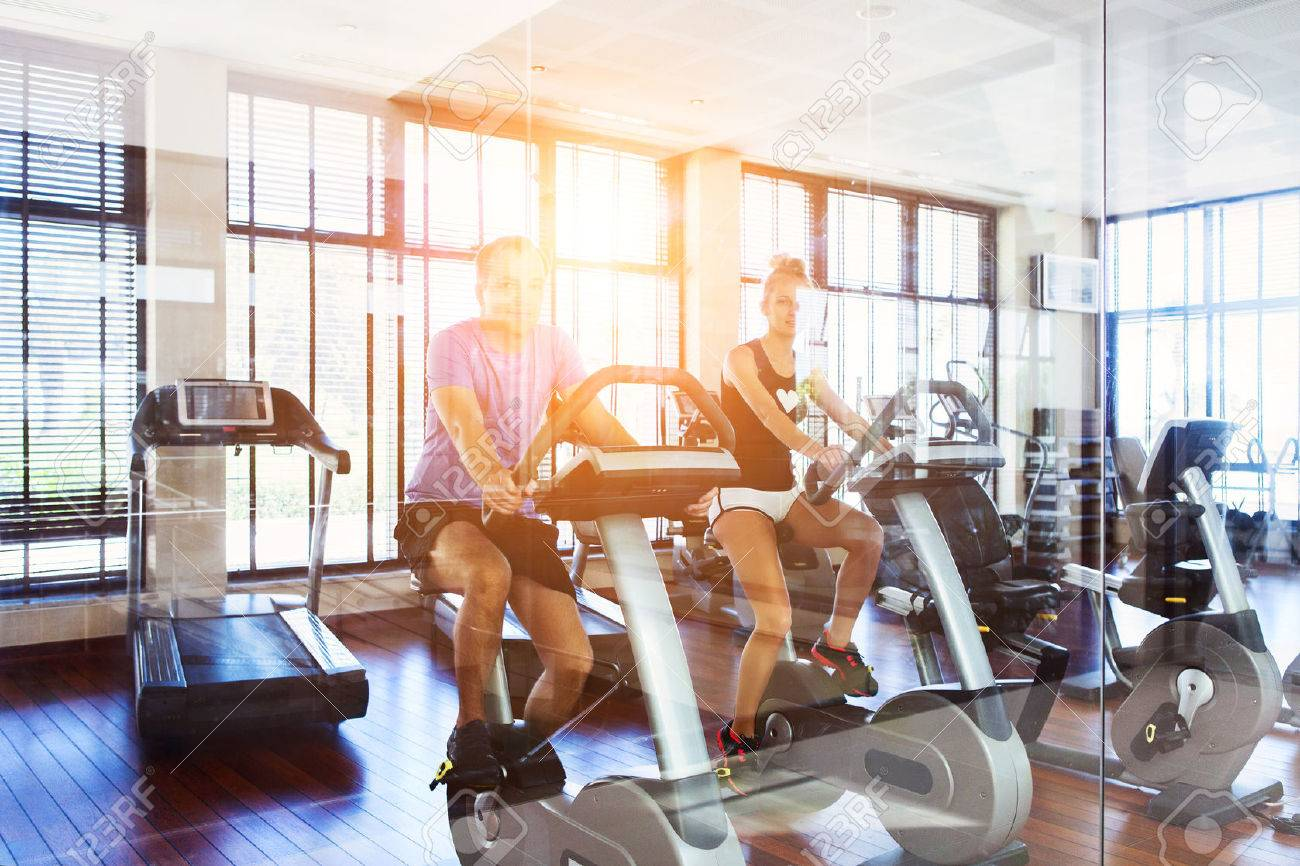 Healthy couple training on a treadmill in a sport center - 45392463
