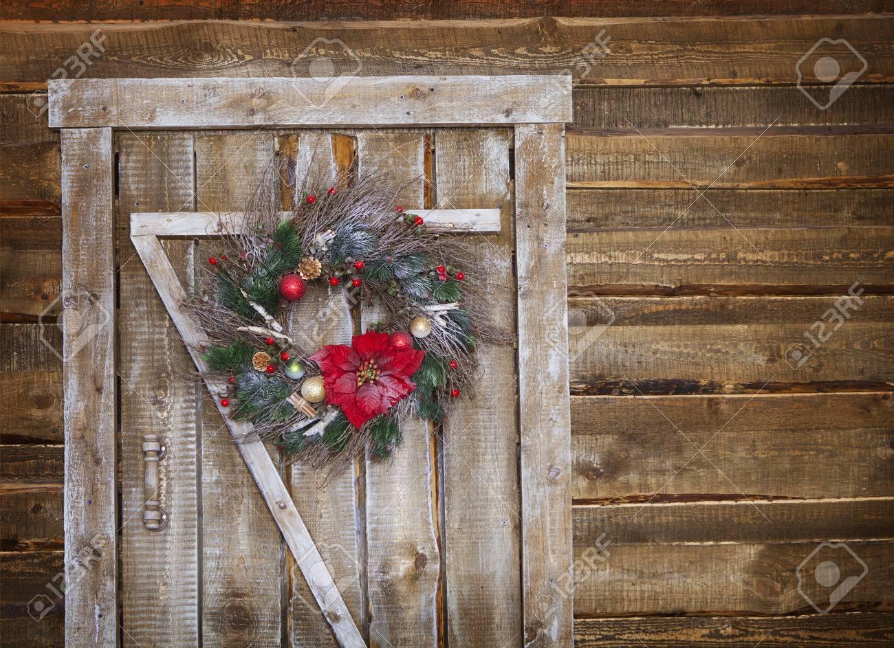 Christmas wreath on a rustic wooden front door - 47008384
