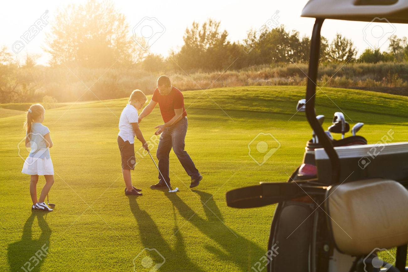 Casual kids at a golf field holding golf clubs studing with trainer. Sunset - 46245960