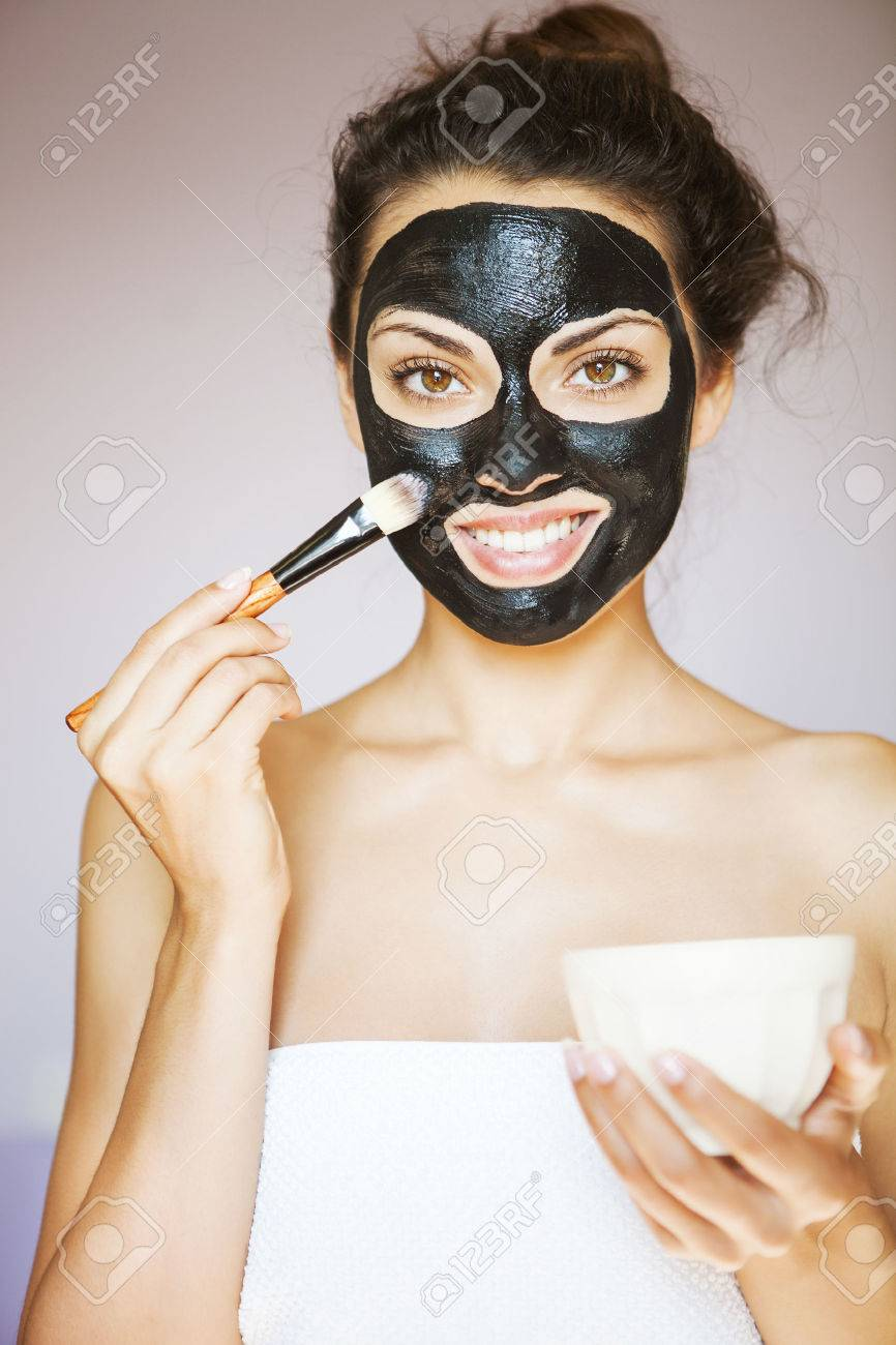 Young beautiful woman applying a mask for the face of the therapeutic black mud. Spa treatment - 46965046