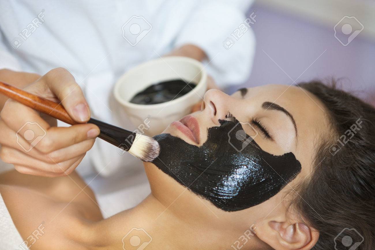 Young beautiful woman in a mask for the face of the therapeutic black mud. Spa treatment - 46965186