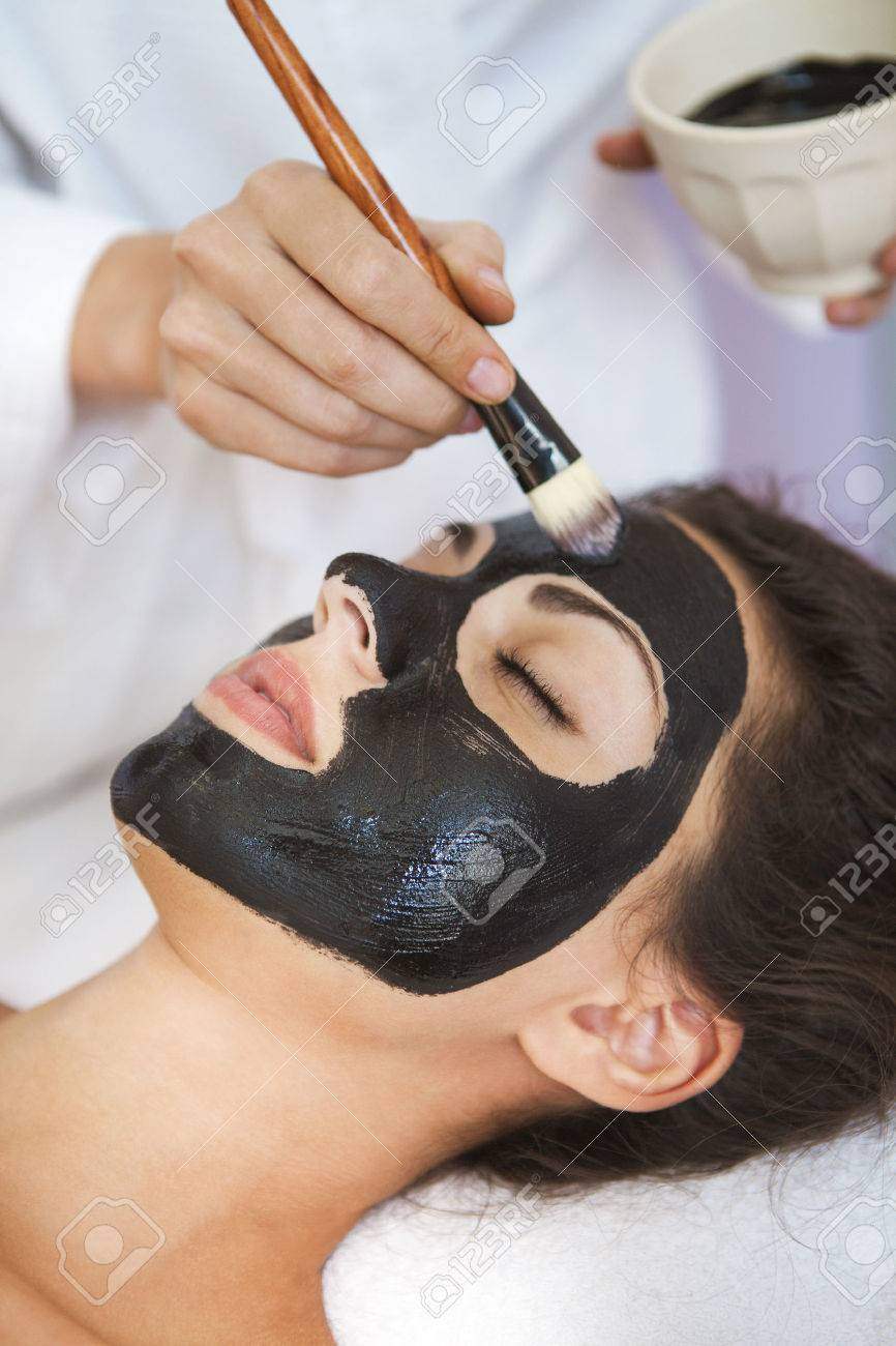 Young beautiful woman in a mask for the face of the therapeutic black mud. Spa treatment - 47219351