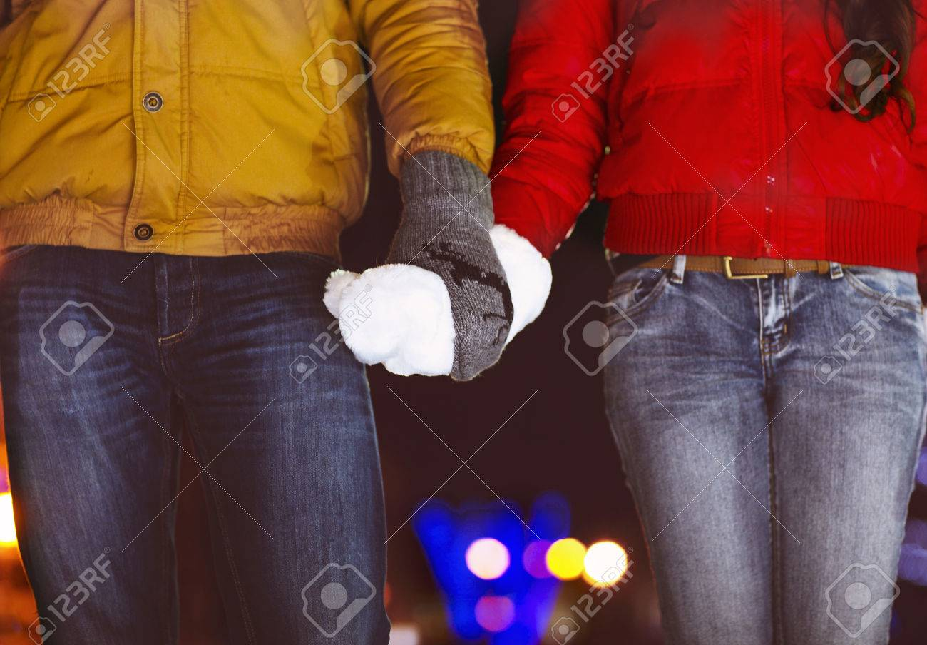 Happy couple holding hands in knitted mittens. Close up - 47219349