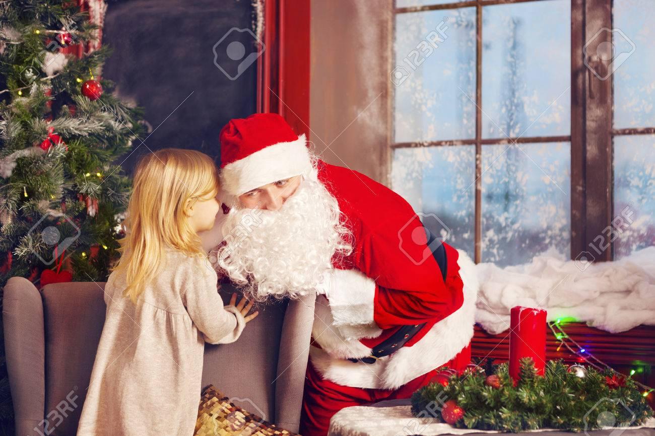 The Christmas Wish.Santa Claus And Little Girl Christmas Scene Girl Telling Her