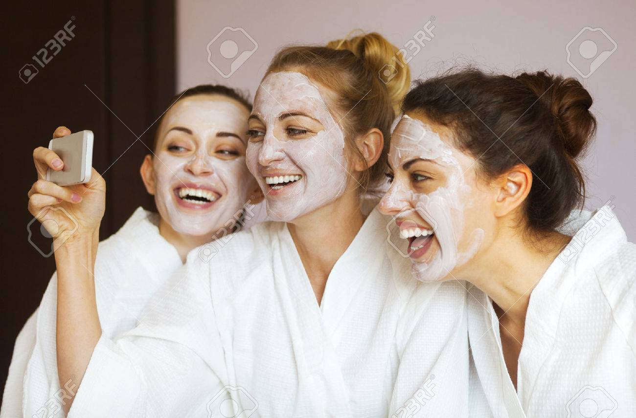 Three young happy women with face masks taking selfi at spa resort. Frenship and wellbeing concept - 47467846