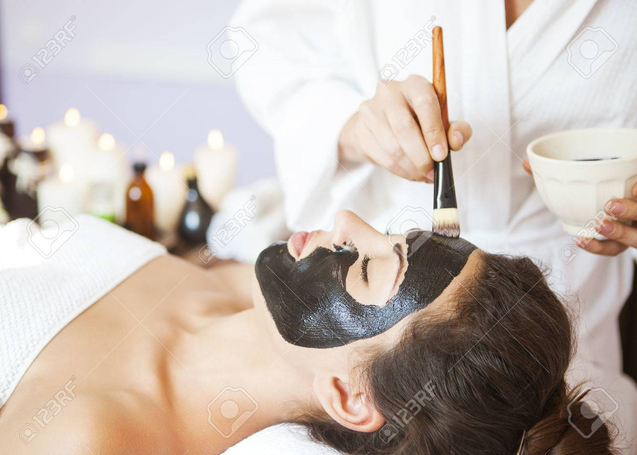 Young beautiful woman in a mask for the face of the therapeutic black mud. Spa treatment - 47707835