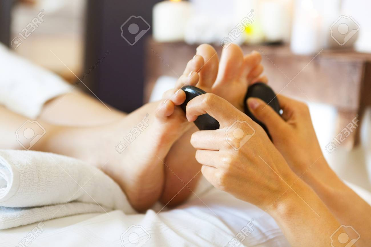 Massage of female foot in spa salon. Healthy lifestyle and relaxation concept. Close up - 48597777