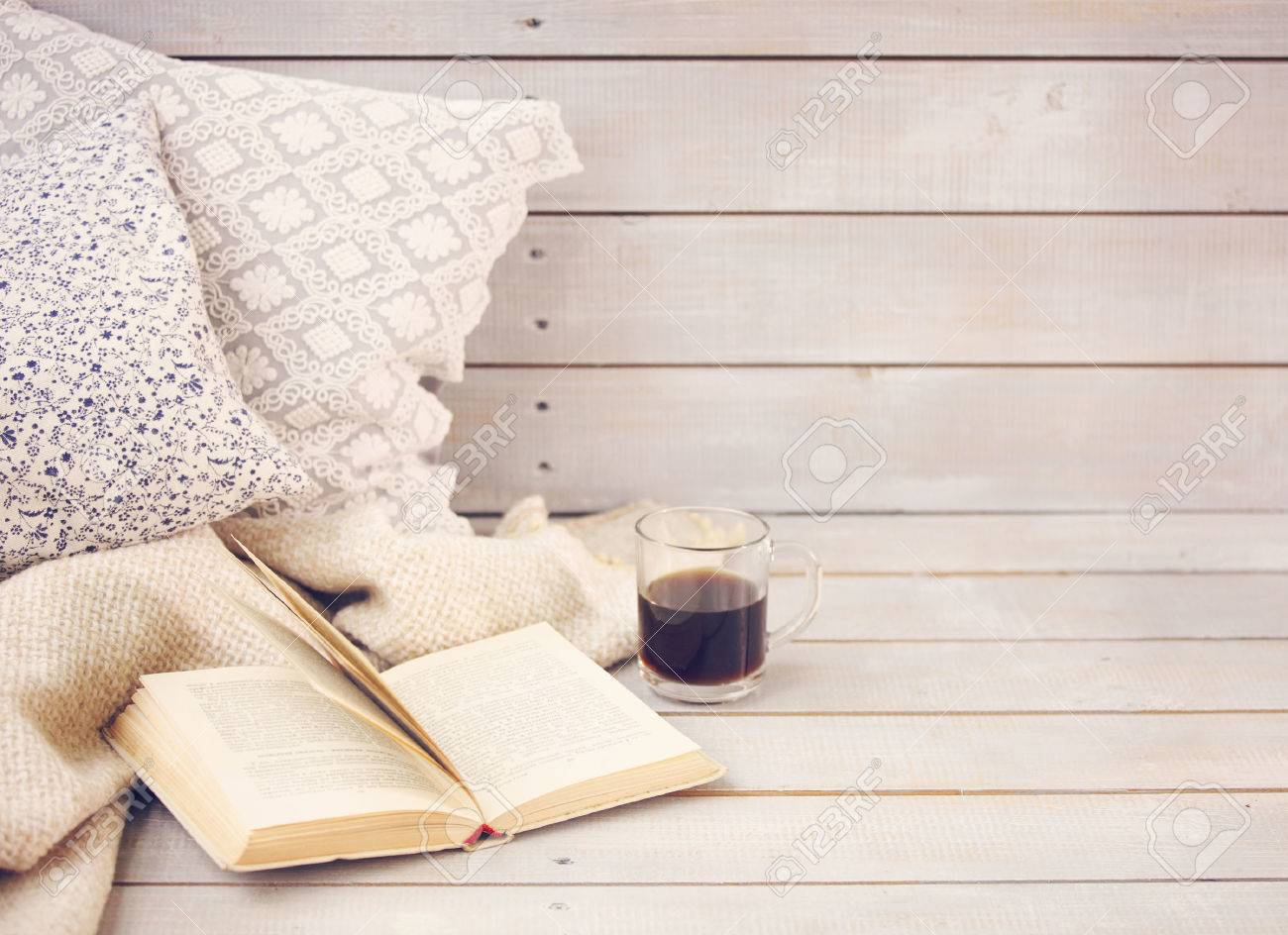 Cozy still life with book, coffee, pillows and plaid on the light wooden background. Close up - 48597783