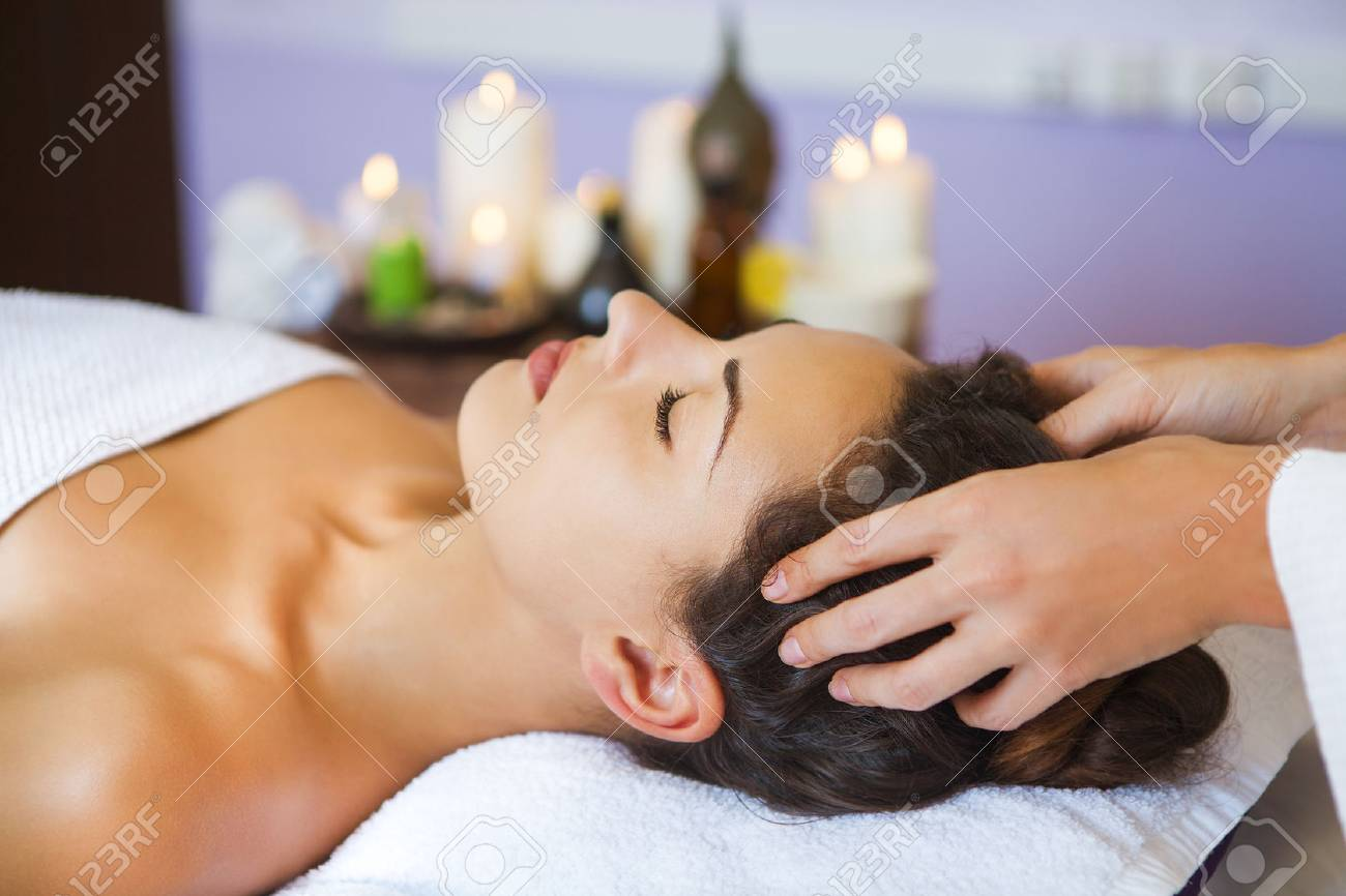 Close up portrait of a young woman getting spa treatment. Head massage - 50767272